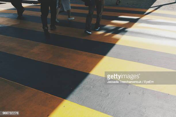 low section of people walking zebra crossing - zebra crossing stock pictures, royalty-free photos & images