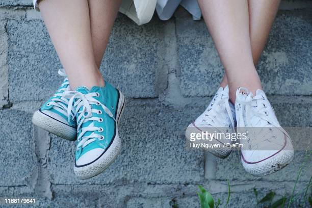 low section of people wearing canvas shoes on footpath - legs crossed at ankle stock pictures, royalty-free photos & images