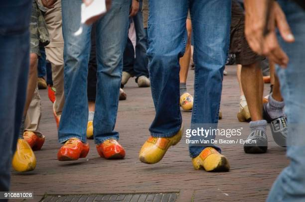 Low Section Of People Wearing Clogs Walking On Floor