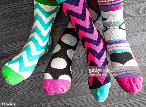 Low Section Of People Wearing Colorful Socks On Hardwood Floor