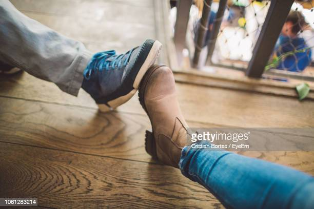 Low Section Of People Wearing Shoes On Wooden Floor