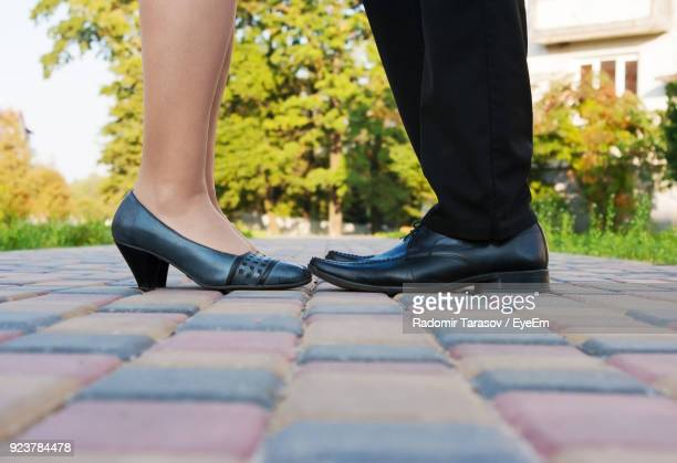 low section of people wearing shoes standing on footpath - sapato preto - fotografias e filmes do acervo