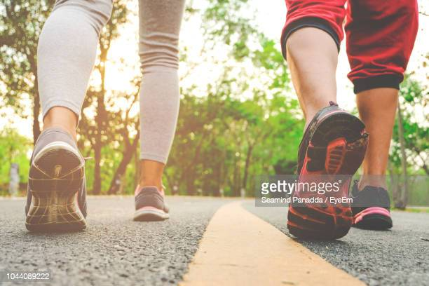 low section of people wearing sports clothing while walking on road - miembro parte del cuerpo fotografías e imágenes de stock