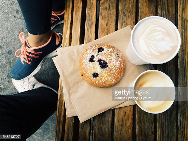 Low Section Of People With Cookie And Cappuccino On Table