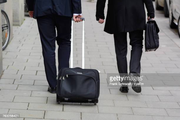 Low Section Of People With Luggage Walking On Street