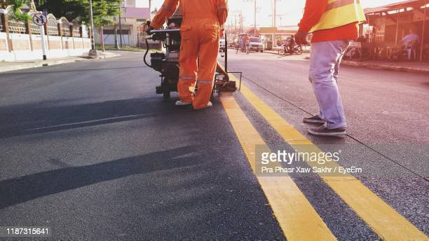low section of people working on road in city - low section stock pictures, royalty-free photos & images