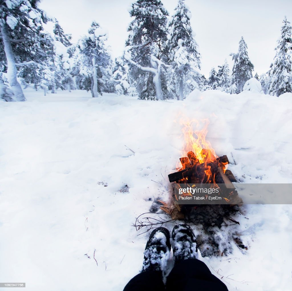 Low Section Of Person Against Bonfire On Snow Covered Field : Stockfoto
