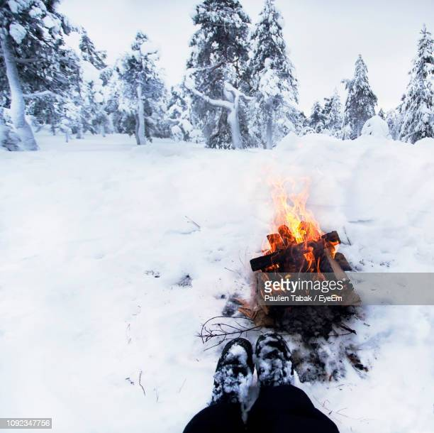 low section of person against bonfire on snow covered field - paulien tabak stockfoto's en -beelden