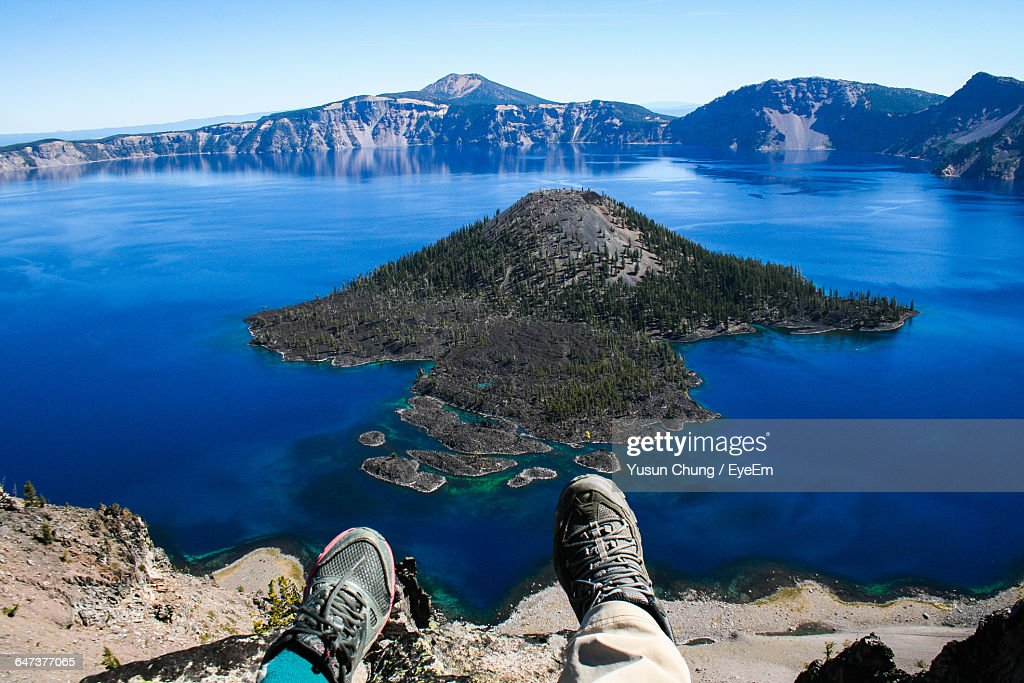 Low Section Of Person Against Crater Lake : Stock Photo