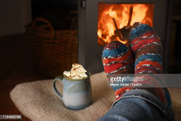 low section of person against fireplace and by cup - sock stock pictures, royalty-free photos & images