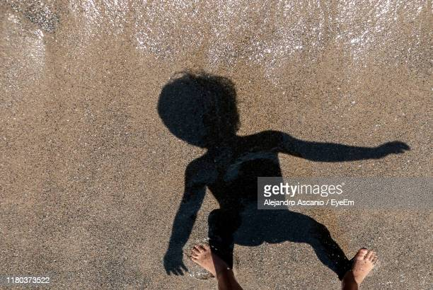 low section of person and shadow on sand - alejandro ascanio fotografías e imágenes de stock