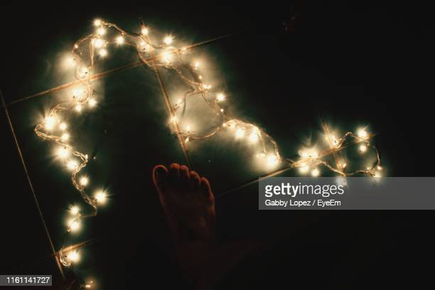 low section of person by illuminated string light on tiled floor at night - gabby lopez stock pictures, royalty-free photos & images