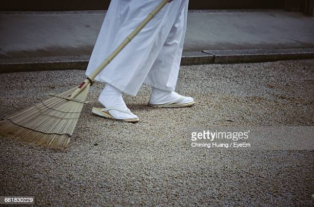 low section of person cleaning footpath with broom - 掃く ストックフォトと画像