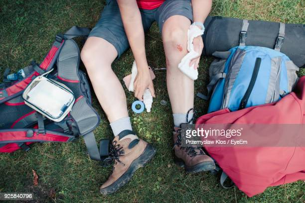 low section of person cleaning wound on grassy field - leg wound stock pictures, royalty-free photos & images
