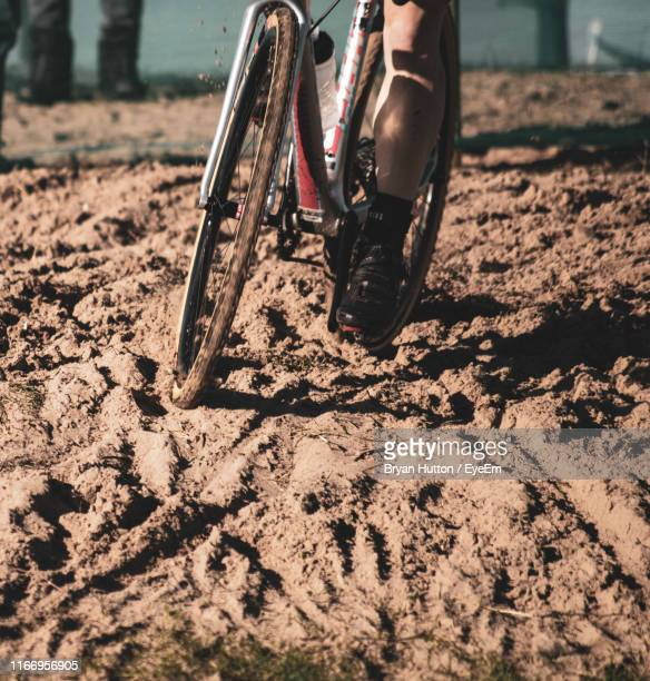 Low Section Of Person Cycling On Sand
