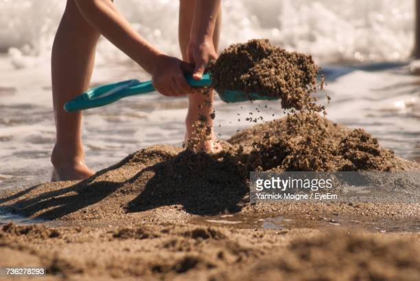 Low Section Of Person Digging On Beach Against Sky