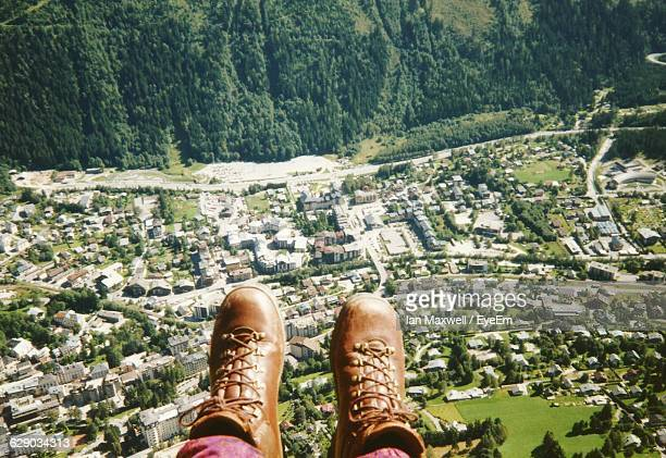 Low Section Of Person Hanging Feet Over Landscape