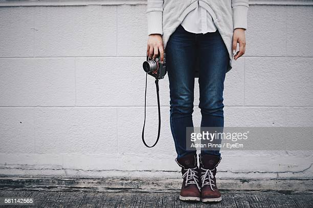 Low Section Of Person Holding Digital Camera
