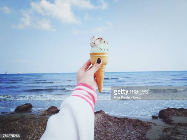 Low Section Of Person Holding Ice Cream At Beach Against Sky