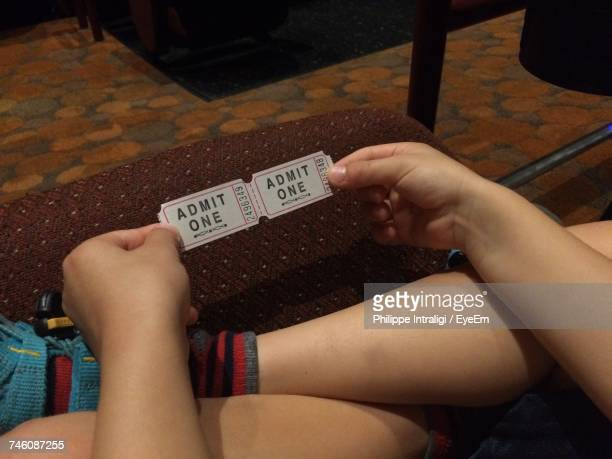 Low Section Of Person Holding Movie Tickets