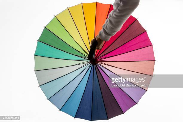 Low Section Of Person Holding Multi Colored Umbrella Against White Background