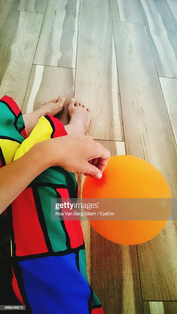 Low Section Of Person Holding Orange Balloon On Floor At Home : Stock Photo
