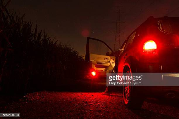 low section of person in car on field at night - tail light stock pictures, royalty-free photos & images