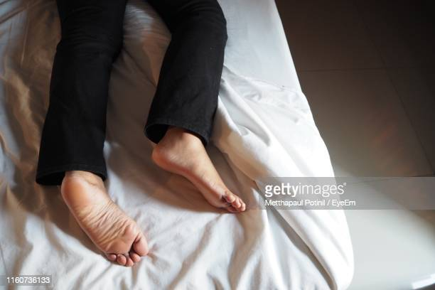 low section of person lying on bed at home - metthapaul stock photos and pictures
