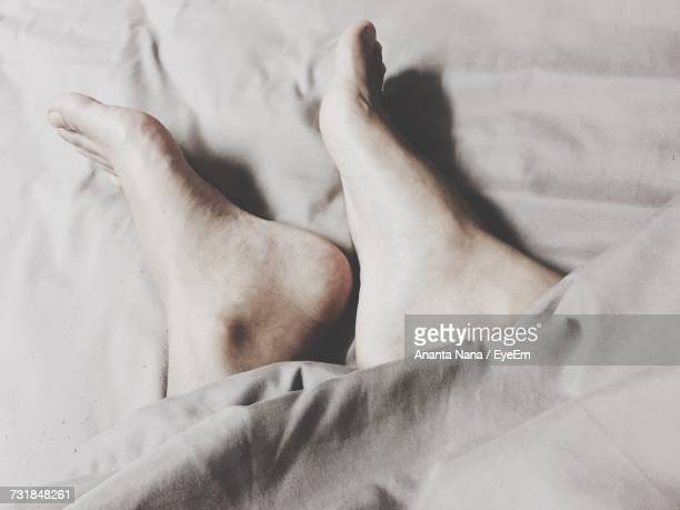 Low Section Of Person On Bed