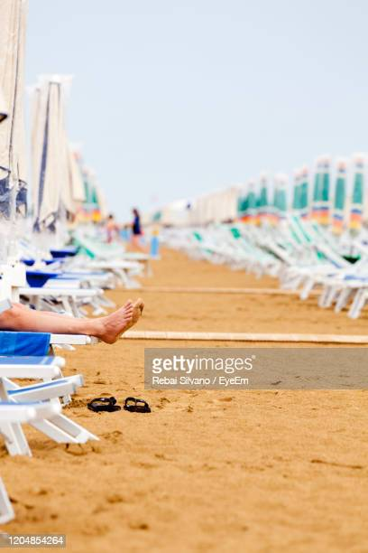 low section of person on chair at beach against sky - rebai silvano foto e immagini stock