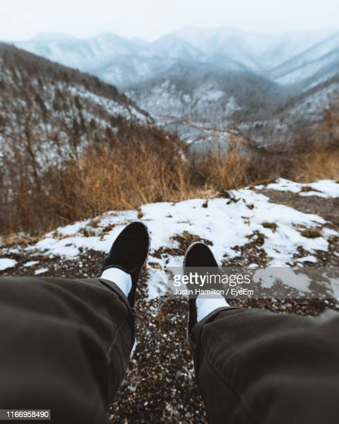low section of person on land against mountains - hamiltonmusical stockfoto's en -beelden