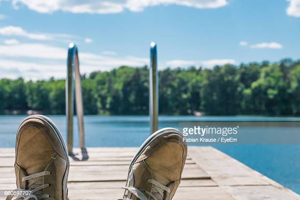 Low Section Of Person On Pier Over Lake
