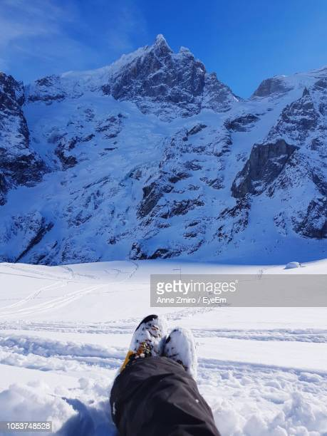 low section of person on snow covered field against mountains - sezione inferiore foto e immagini stock
