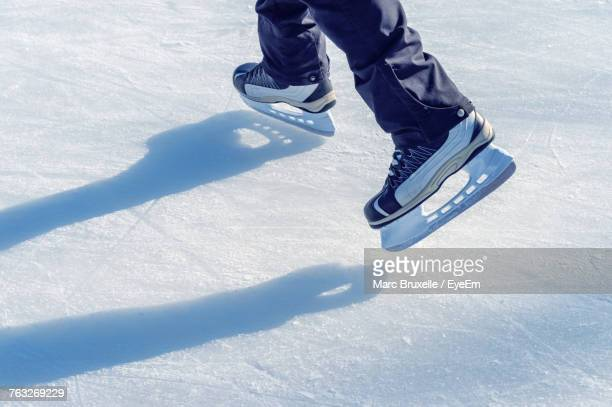 low section of person on snow covered field - ice skate stock pictures, royalty-free photos & images