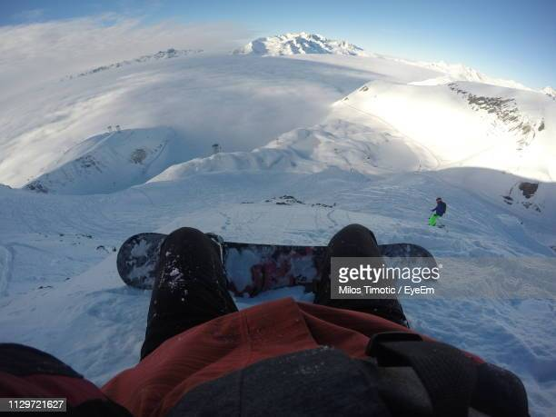 low section of person on snow covered mountain - sezione inferiore foto e immagini stock