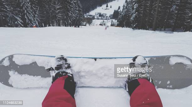 low section of person on snowboard at snowfield - winter sport stock pictures, royalty-free photos & images