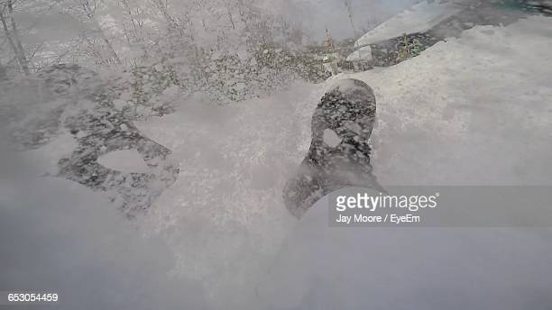 Low Section Of Person On Snowcapped Field During Winter