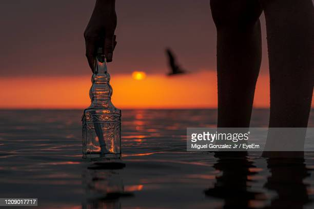 low section of person on wooden post at sea during sunset - south padre island stock pictures, royalty-free photos & images