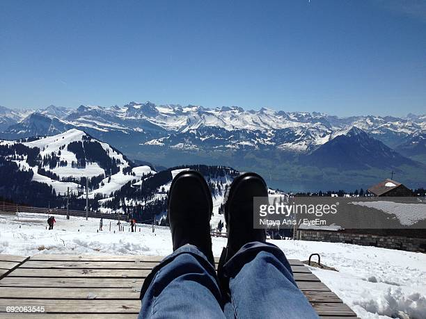 Low Section Of Person On Wooden Sea At Snow Covered Field By Mountains Against Clear Sky