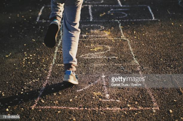low section of person playing hopscotch on street - hopscotch stock pictures, royalty-free photos & images