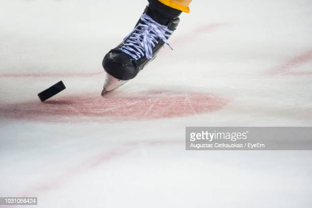 low section of person playing ice hokey in rink - ice hockey stock pictures, royalty-free photos & images