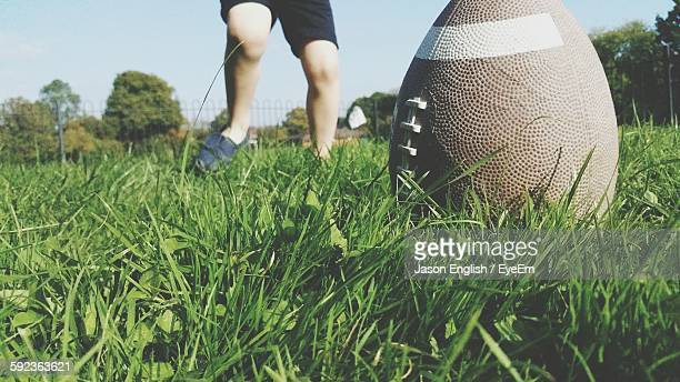 low section of person playing with rugby ball on grassy field - rugby pitch stock pictures, royalty-free photos & images