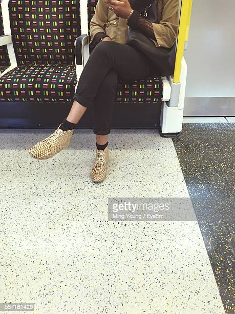 Low Section Of Person Relaxing In Subway Train