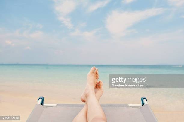 low section of person relaxing on beach - legs crossed at ankle stock pictures, royalty-free photos & images