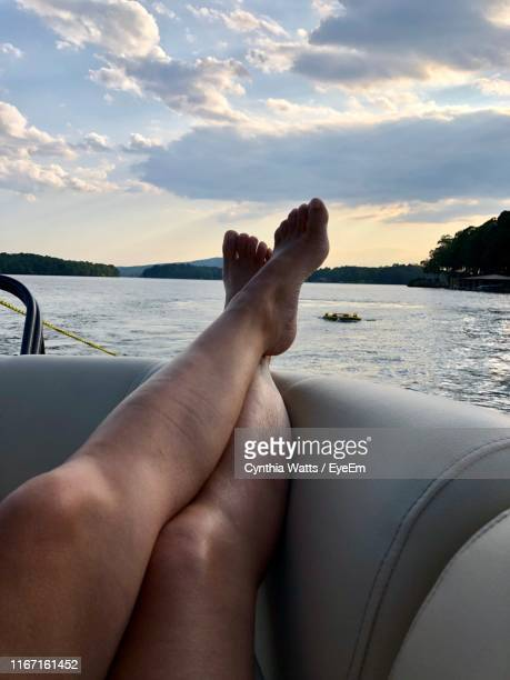 low section of person relaxing on boat in sea against sky - menschliches bein stock-fotos und bilder