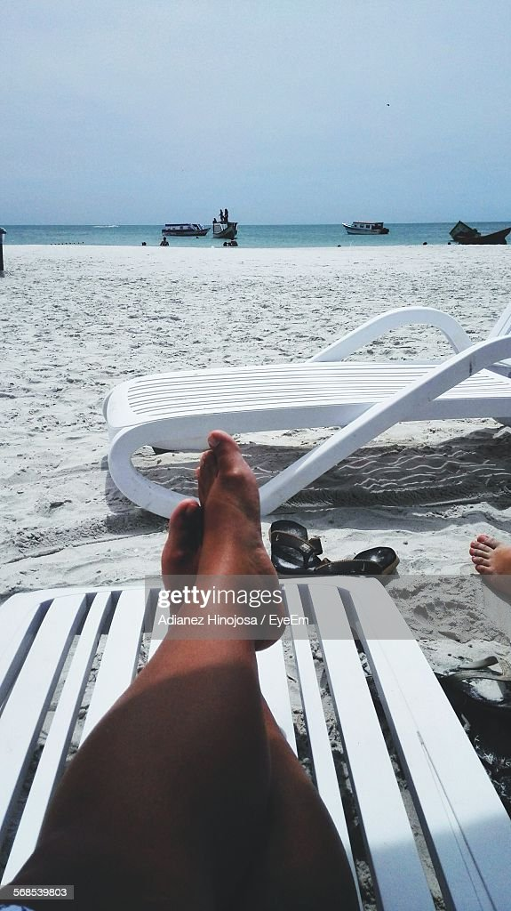 Low Section Of Person Relaxing On Lounge Chair At Beach Against Sky : Stock Photo