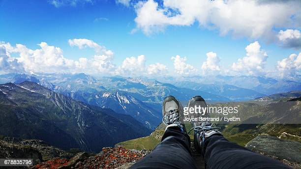 Low Section Of Person Relaxing On Mountain Against Cloudy Sky