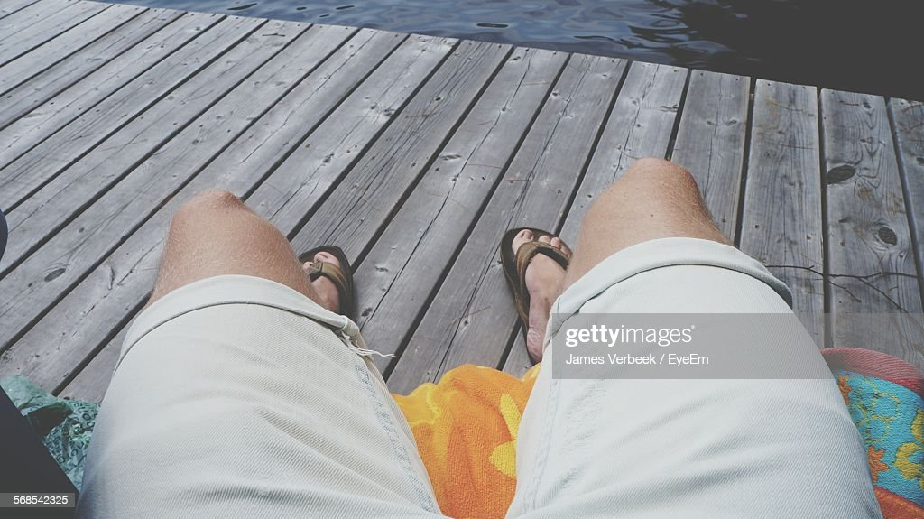 Low Section Of Person Relaxing On Pier : Stock Photo