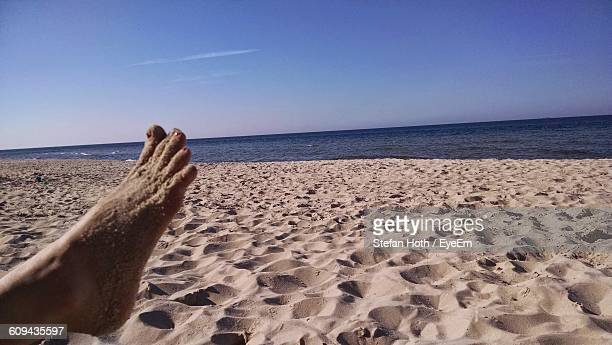 Low Section Of Person Relaxing On Sandy Beach
