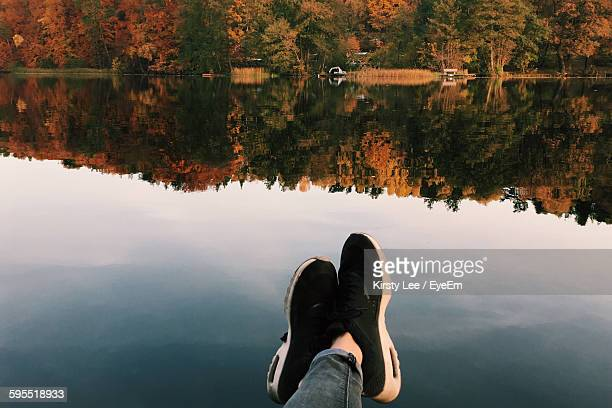 Low Section Of Person Resting By Calm Lake During Autumn